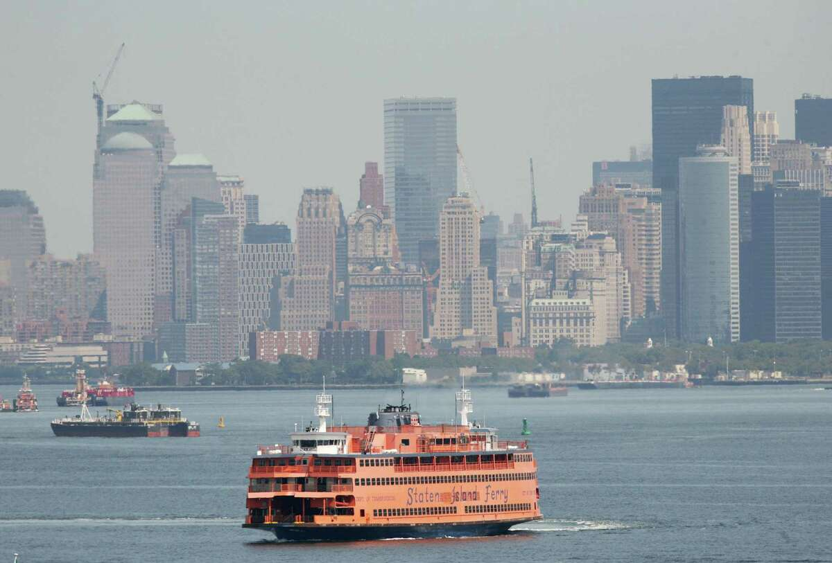 FILE - In this Aug. 27, 2008 file photo, the Staten Island Ferry crosses New York Harbor past the Manhattan skyline in New York. The ferry ride is one of the city's best free attractions for visitors, offering great views of the statue, the harbor and the skyline.