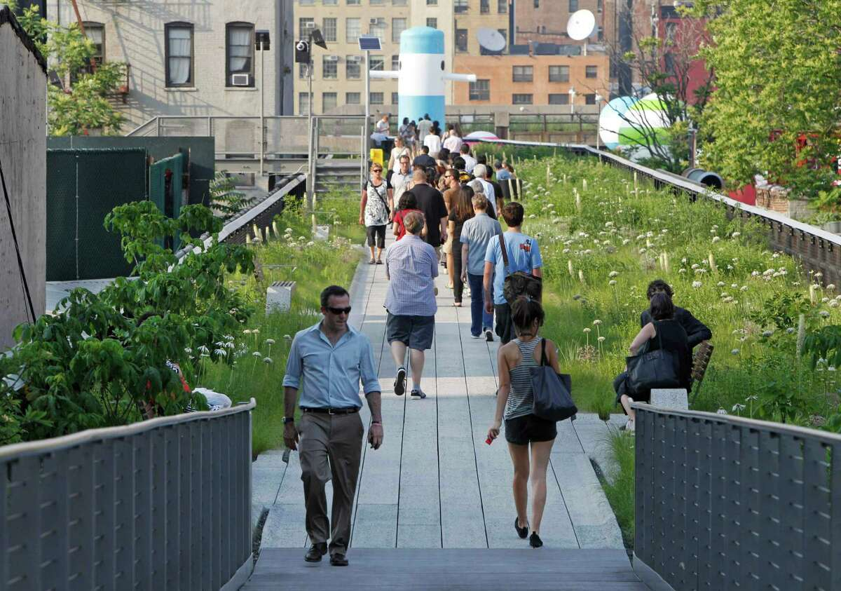 FILE - In this June 7, 2011 file photo, visitors stroll down a walkway after the second section of the High Line, an industrial era elevated railway converted into a city park, opened to the public one day early in New York. The High Line is built on an old elevated freight line along 10th Avenue, on Manhattan's West Side. It offers unusual views of the city from 30 feet above ground and is one of New York's best free attractions.