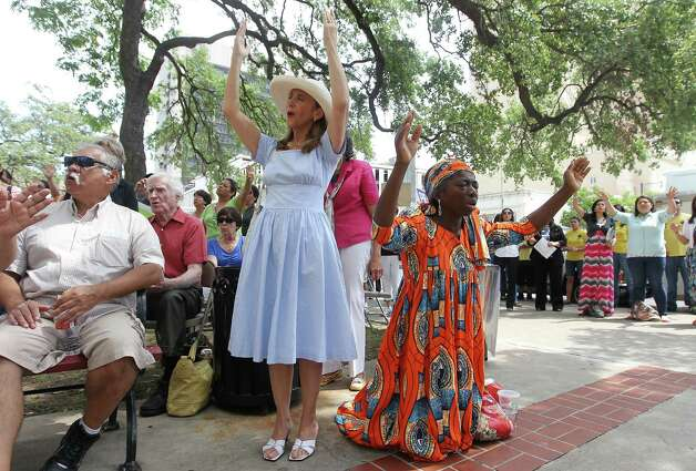 Patricia Moore (second from left) and Francisca McNair both raise their arms in prayer and song as they join other Christians at the steps of City Hall for National Day of Prayer on Thursday, May 3, 2012. Photo: KIN MAN HUI, San Antonio Express-News / ©2012 San Antonio Express-News
