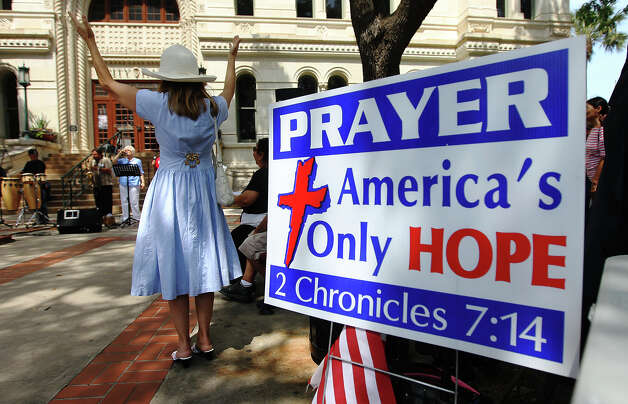 Patricia Moore (left) raises her hands in prayer as Christians gather at the steps of City Hall for National Day of Prayer on Thursday, May 3, 2012. Photo: KIN MAN HUI, San Antonio Express-News / ©2012 San Antonio Express-News
