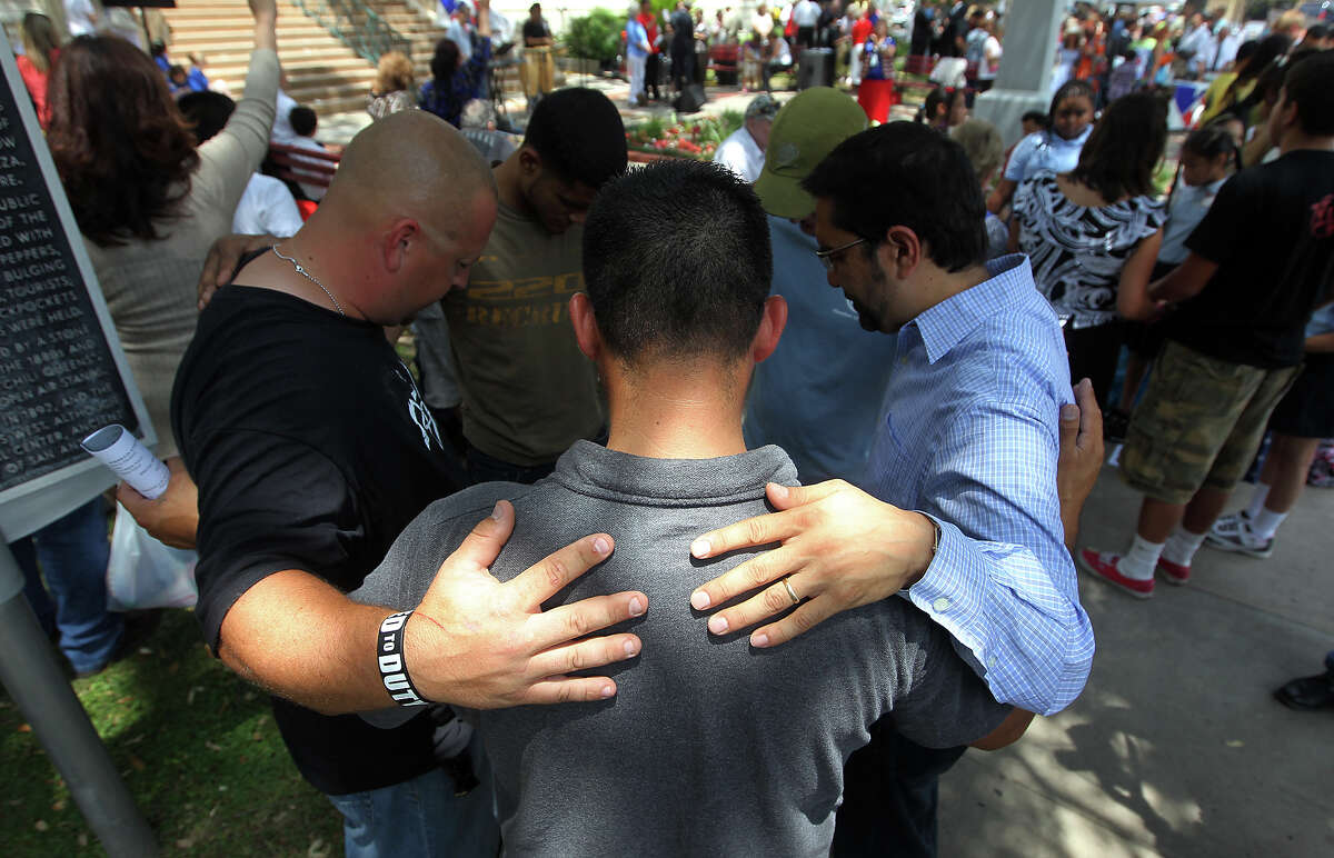 A group of men gather in a circle to pray as they join other Christians at the steps of City Hall for National Day of Prayer on Thursday, May 3, 2012.