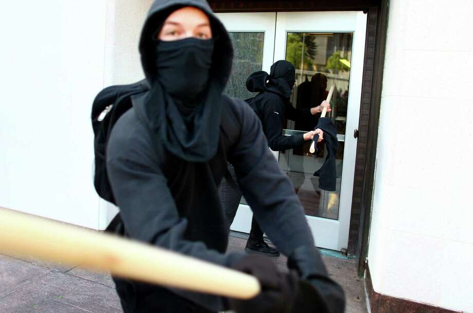 Black-clad protesters break windows on the old Federal Courthouse building during a May Day rally on Tuesday, May 1, 2012 in downtown Seattle. Photo: JOSHUA TRUJILLO / SEATTLEPI.COM