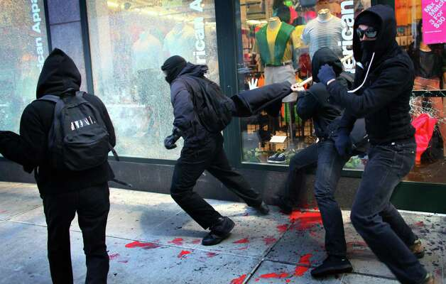 Black-clad protesters break windows on American Apparel during a May Day rally on Tuesday, May 1, 2012 in downtown Seattle. Photo: JOSHUA TRUJILLO / SEATTLEPI.COM