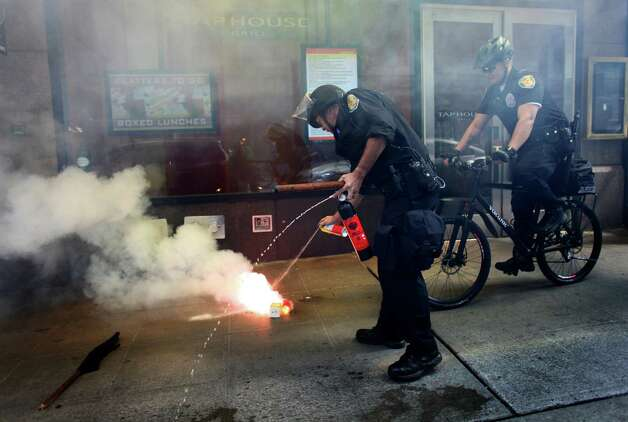 A Seattle Police officer extinguishes an incendiary device thrown by a protester during a May Day rally on Tuesday, May 1, 2012 in downtown Seattle. The device appeared to be made from a roll of toilet paper and juice boxes. Photo: JOSHUA TRUJILLO / SEATTLEPI.COM
