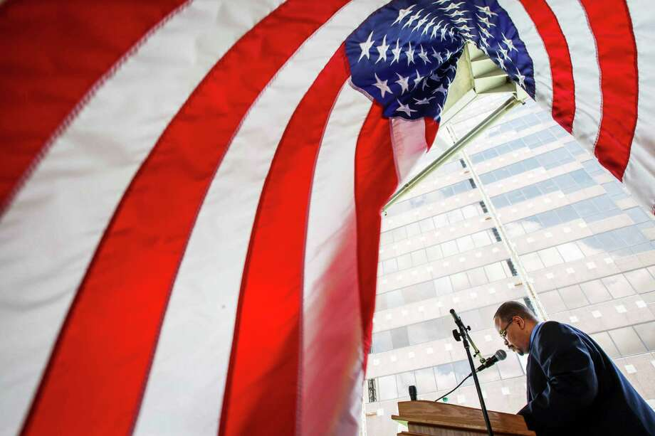 "Reese Williams reads a prayer as people gather for the 61st annual observance of the National Day of Prayer outside the George Thomas ""Mickey"" Leland Federal Building, Thursday, May 3, 2012, in Houston. Photo: Michael Paulsen, Houston Chronicle / © 2012 Houston Chronicle"