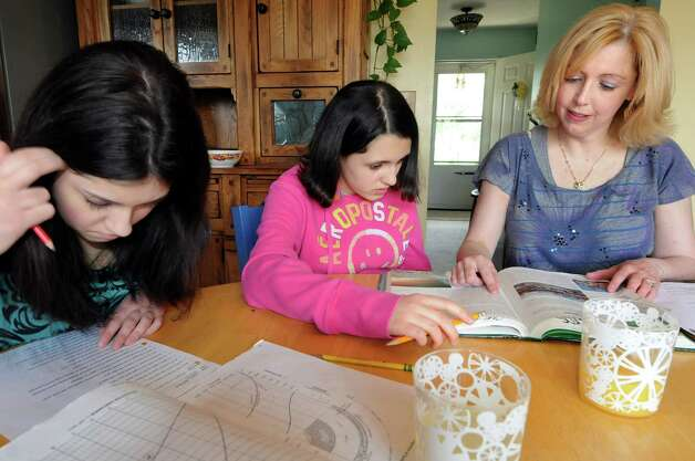 "Eileen Riley-Hall, right, helps her daughters Lizzie Walther, 15, left, and Caroline Walther, 13, with their homework on Saturday, April 28, 2012, at their home in Ballston Lake, N.Y Riley-Hall has written a book entitled ""Parenting Girls on the Autism Spectrum."" (Cindy Schultz / Times Union) Photo: Cindy Schultz / 00017463A"