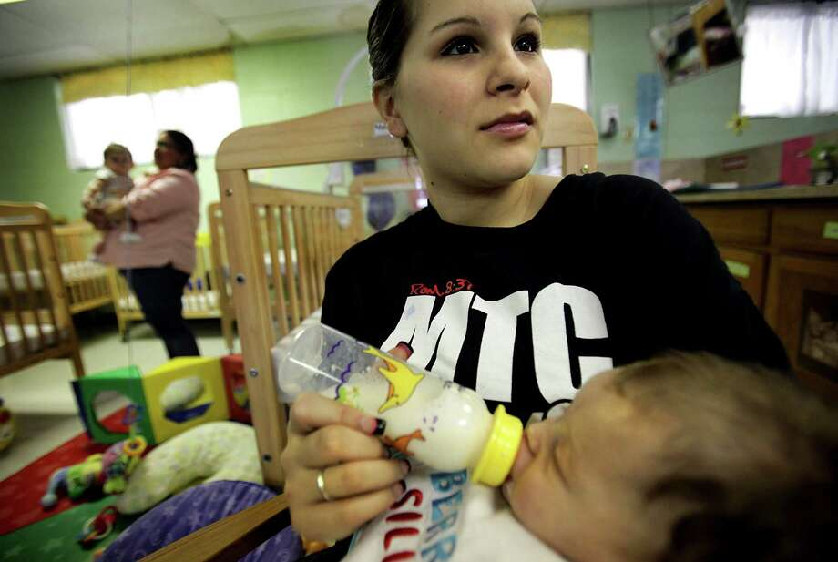 Miranda Berdecia, a 17 yr old mother, is finishing up her high school degree at Healy Murphy, feeds her baby Matthew in the day care center.  Thursday, Feb. 2, 2012. Bob Owen/Express-News Photo: BOB OWEN, San Antonio Express-News / © 2012 San Antonio Express-News