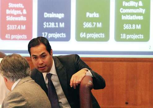 Mayor Julian Castro (center) confers with District 6 councilman Ray Lopez as a screen shot of estimated costs for various city projects shows on a screen during a presentation for a proposed upcoming city bond election at City Council Chambers on Thursday, Jan. 12, 2012. If approved by council, the election will go to the voters on May 12. Kin Man Hu/kmhui@express-news.net Photo: Kin Man Hui, SAN ANTONIO EXPRESS-NEWS / San Antonio Express-News