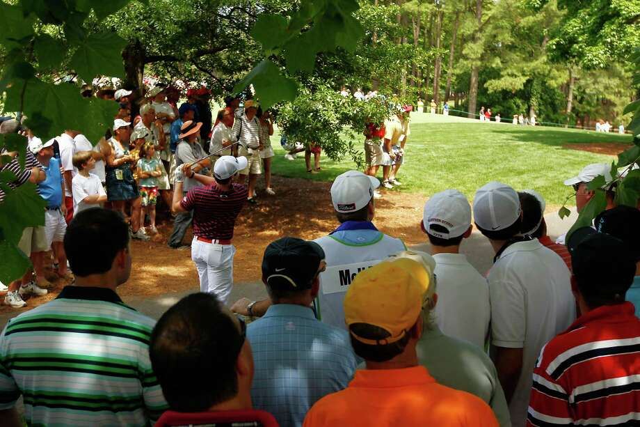 Patrons watch as Rory McIlory of Northern Ireland hits out of the pine needles on the fifth hole during the first round of the Wells Fargo Championship at the Quail Hollow Club on May 3, 2012 in Charlotte, North Carolina. Photo: Mike Ehrmann, Getty Images / 2012 Getty Images