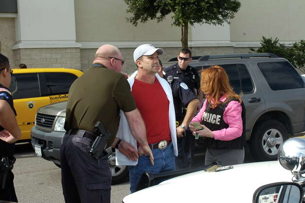 "A robbery suspect, center, in baseball hat, has been taken into custody near Dillard's at Parkdale Mall. Police believe the man is the so-called ""tall, dark and handsome"" bandit who robbed banks in Houston and Beaumont over the past week.  Officers stopped the man as he tried to get into a taxi outside of Dillard's.    Dave Ryan/The Enterprise"