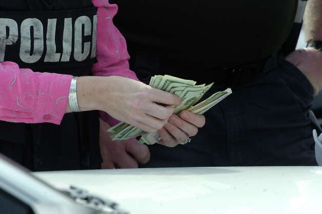"Law enforcement officials count money taken from the suspect outside Parkdale Mall near Dillard's.   Police believe the man they have in custody is the so-called ""tall, dark and handsome"" bandit who robbed banks in Houston and Beaumont over the past week.  Officers stopped the man as he tried to get into a taxi outside of Dillard's.   Dave Ryan/The Enterprise"