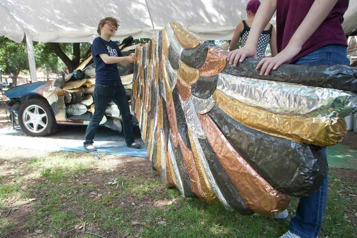 Senior Claire Schaffer and freshman Boying Meng work on the wing of the Owl Car at Rice University. The car will be entered into the Houston Art Car Parade.