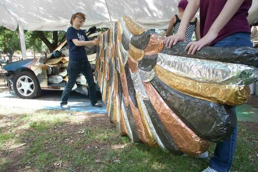 Senior Claire Schaffer and freshman Boying Meng work on the wing of the Owl Car at Rice University.  The car will be entered into the Houston Art Car Parade. Photo: J. Patric Schneider / Houston Chronicle