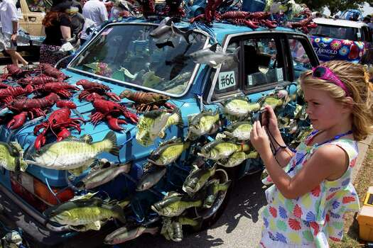 Ava Grace Sweitzer, 6, of Houston, takes a picture of her favorite Art Car, The Singing Fish, before the 2011 parade. Photo: Nick De La Torre / © 2010 Houston Chronicle