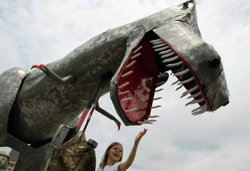 Sacha Waters, 5, of Houston, plays with the teeth of a dinosaur Art Car, in 2010. Photo: Nick De La Torre / Houston Chronicle