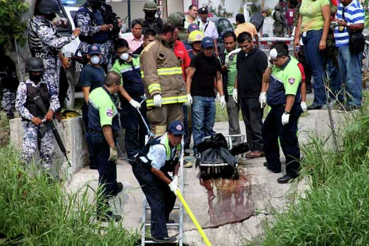 Police remove from a canal plastic bags containing the dismembered bodies of four people in Boca del Rio, Mexico, Thursday, May 3, 2012. The bodies were found dumped together in plastic bags by a canal in the eastern Mexican state of Veracruz on Thursday, less than a week after the killing of a reporter for an investigative newsmagazine. At least three of the slain had worked as news photographers.