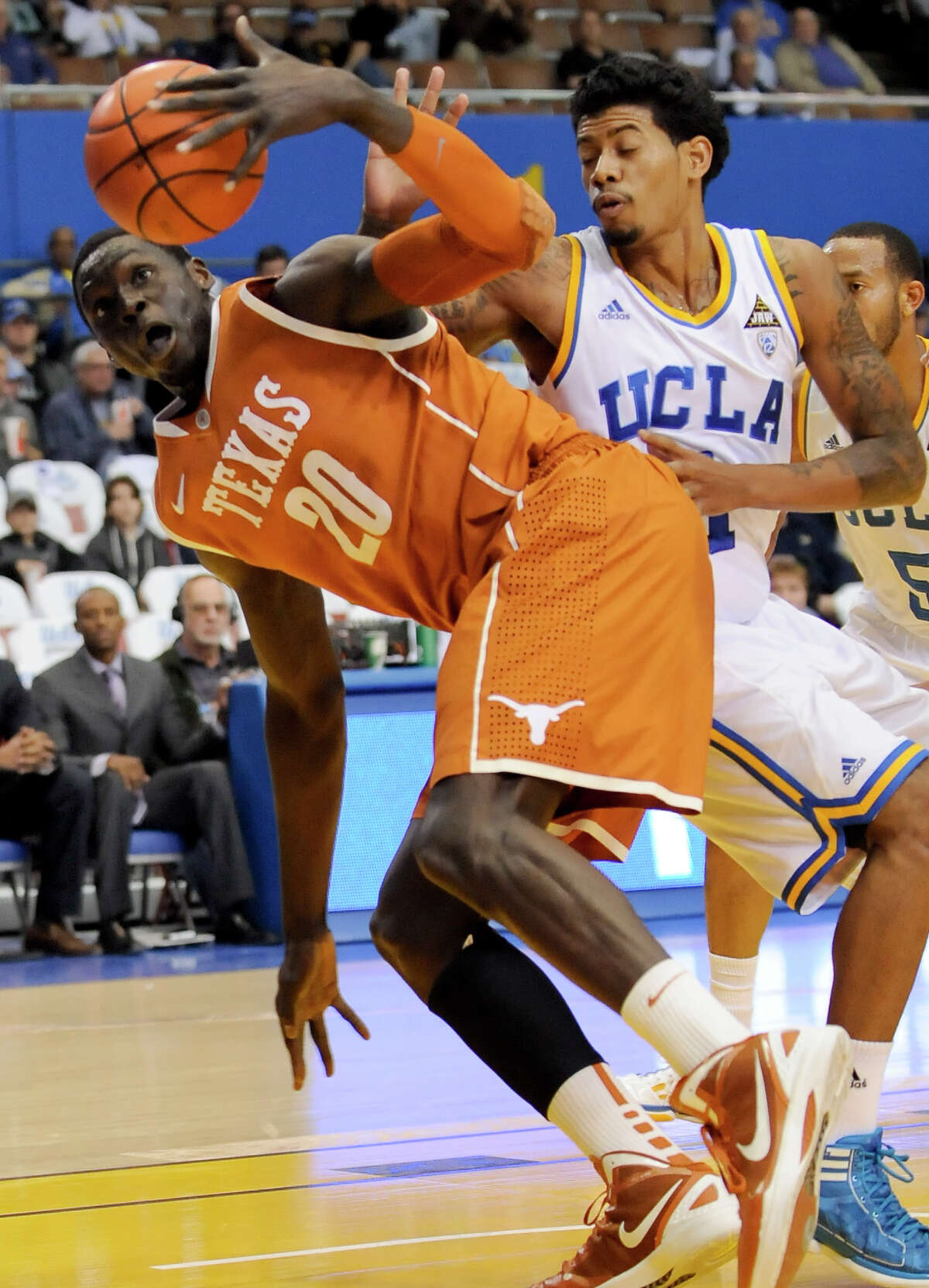 Texas forward/center Alexis Wangmene (20) and UCLA guard Tyler Lamb, right, fight for a loose ball during the first half of an NCAA college basketball game on Saturday, Dec. 3, 2011, in Los Angeles.