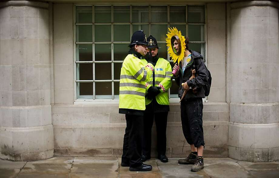 Sun, you shouldn't be here:Two London coppers accost a protester near St Paul's Cathedral during a demonstration against the use of fossil fuels and the policies of energy firms attending the the UK Energy Summit. Photo: Leon Neal, AFP/Getty Images