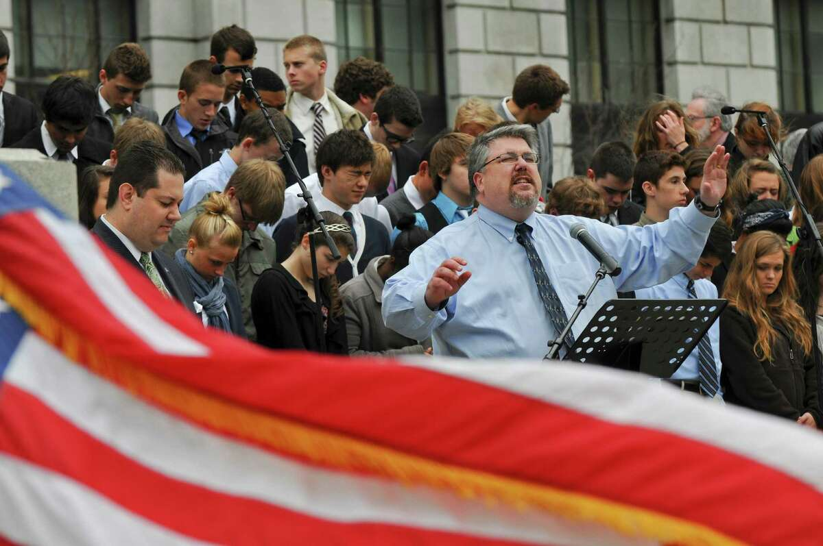 Ernie North, Pastor of Fruitful Vine Christian Church, of Ballston Lake, leads the crowd in praying for the country and our leaders during the 61st National Day of Prayer, in West Capitol Park, on Thursday May 3, 2012 in Albany, NY. Behind him are students from the Loudonville Christian School Choir. (Philip Kamrass / Times Union )