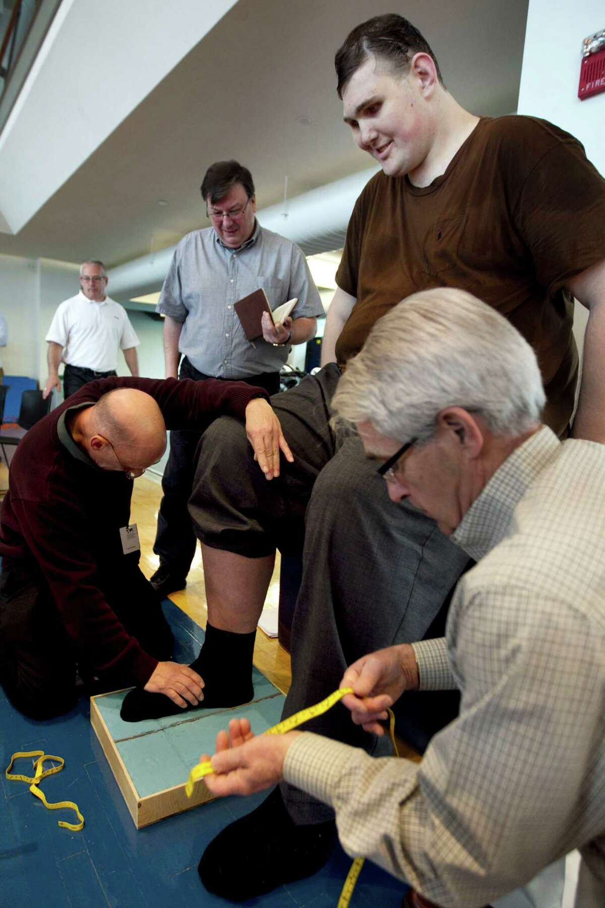 Igor Vovkovinskiy, of Minneapolis, currently the tallest man in the United States at seven feet eight inches, has an imprint taken of his foot by technicians as part of a shoe fitting at Reebok headquarters, in Canton, Mass., Thursday, May 3, 2012. Vovkovinskiy, who has a shoe size between 22 and 26, says he's had 16 surgeries in six years to fix problems created by shoes that didn't fit. Reebok is providing the shoes at no charge. (AP Photo/Steven Senne)
