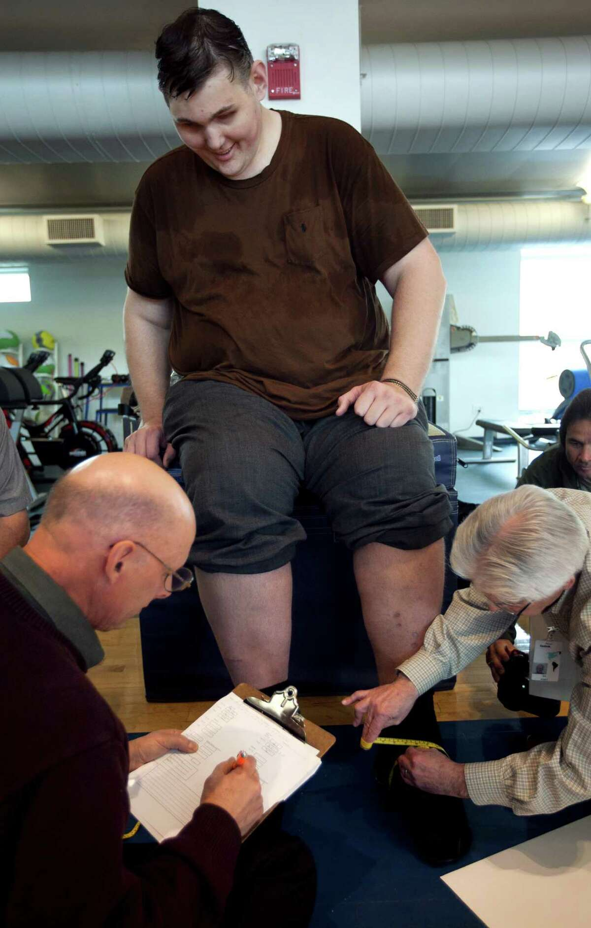 Igor Vovkovinskiy, of Minneapolis, currently the tallest man in the United States at seven feet eight inches, has his feet measured by shoe technicians as part of a shoe fitting at Reebok headquarters, in Canton, Mass., Thursday, May 3, 2012. Vovkovinskiy, who has a shoe size between 22 and 26, says he's had 16 surgeries in six years to fix problems created by shoes that didn't fit. Reebok is providing the shoes at no charge. (AP Photo/Steven Senne)