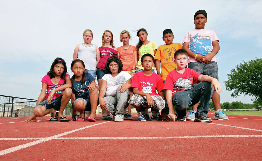 Portrait of some of the Junction elementary school fifth grade students that were told to crawl down the school's track at Eagle Stadium and meow like cats Sheyenne Riojas, 11, (front row from left), Alicia Molina, 11, Lexi Rodriquez, 10, Julian Sauceda, 11, Daniel Hernandez, 10,  (back row from left) Madison Phillips, 11, Lilly Hickenbottom, 11, Ashlynn Pharris, 11, Sierra Carlile, 13, Simon Avila, 12, and Benny Sauceda, 11, Thursday May 3, 2012 in Junction, Tx. Photo: EDWARD A. ORNELAS, SAN ANTONIO EXPRESS-NEWS / © SAN ANTONIO EXPRESS-NEWS (NFS)
