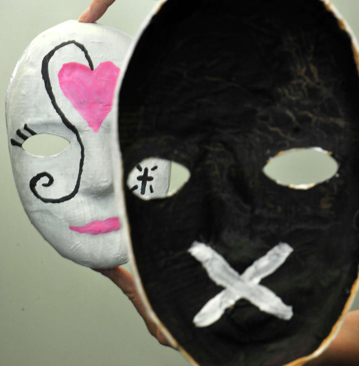 A mask made by a woman in a domestic violence support group shows, in the reflection at left, what the victim shows the world. The inside of the mask, right, represents what the victim is really going through. Photographed at the Women's Center of Greater Danbury on Thursday, May 3, 2012.