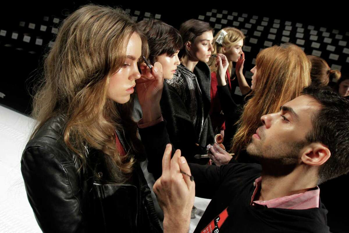 FILE - In this Feb. 15, 2012, file photo, models have their make-up finalized under runway light before the J. Mendel Fall 2012 collection is modeled during Fashion Week, in New York. The 19 editors of Vogue magazines around the world made a pact to project the image of healthy models. They agreed to