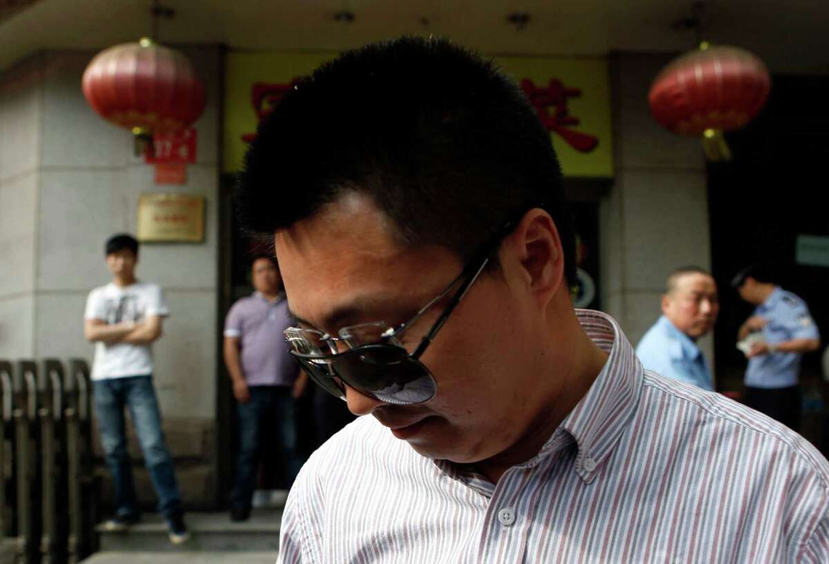 Du Yanling wears sunglasses, similar to those of blind Chinese activist Chen Guangcheng, over his normal glasses outside the hospital where Chen is recuperating in Beijing, China, Thursday, May 3, 2012. Du said he is there to show support for Chen who fled persecution by local officials in his rural town and sought refuge in the U.S. Embassy in Beijing for six days. (AP Photo/Ng Han Guan)