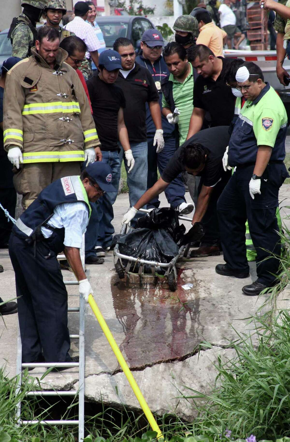 Firefighters and rescuers retrieve plastic bags that held the dismembered corpses of two photojournalists who disappeared Wednesday in the Mexican city port of Veracruz.