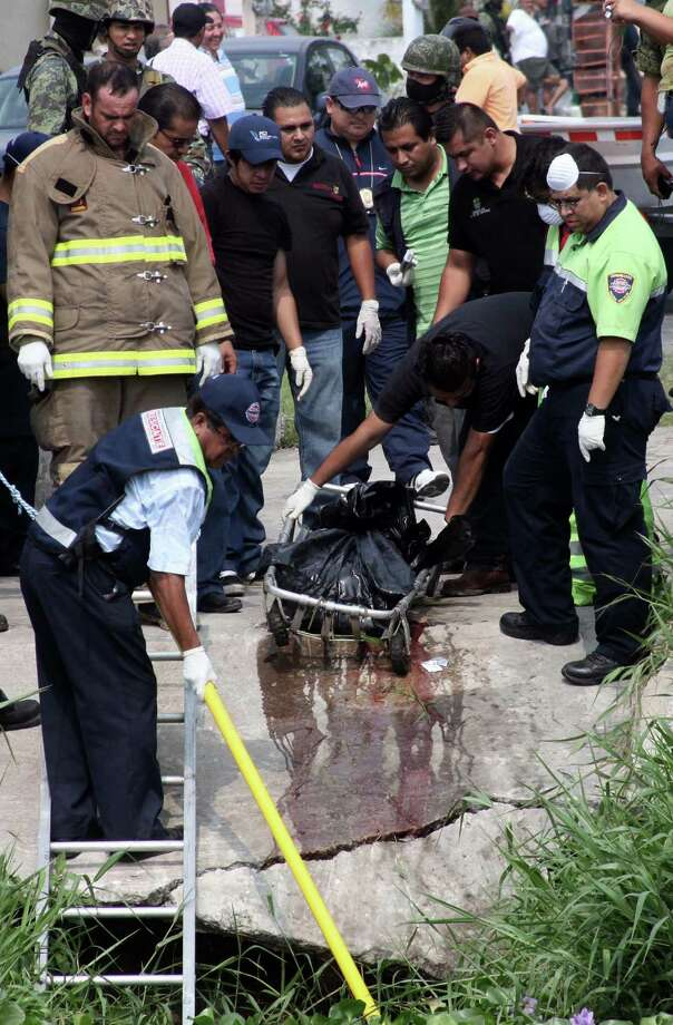 Firefighters and rescuers retrieve plastic bags that held the dismembered corpses of two photojournalists who disappeared Wednesday in the Mexican city port of Veracruz. Photo: LUCAS CASTRO / AFP ImageForum