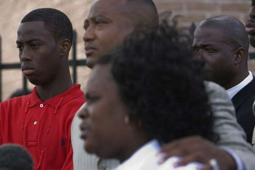 During a press conference outside the South Chase Apartment complex Chad Holley, 15, (left) looks on as community activist Quanell X (center) and Chad's mother, Joyce Holley (right), explain how Chad Holley was allegedly beaten up by Houston police officers last month, Thursday, April 29, 2010, in Houston.