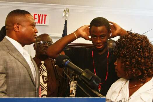 Chad Holley (second from right) demonstrates how he allegedly surrendered before he was beaten and taken to a hospital after an encounter with eight Houston police officers in March, as Minister Quanell X (left) and his mother Joyce Holley (right) look on during a  during a press conference as with members of the NAACP, S.H.A.P.E. Community Center, the Nation of Islam, Ministers Against Crime, the National Black United Front and other community leaders, gather Tuesday, May 4, 2010, in Houston to release graphic images of injuries sustained by a Holley during the incident March 24, 2010 in Houston with eight Houston Police Department officers. 