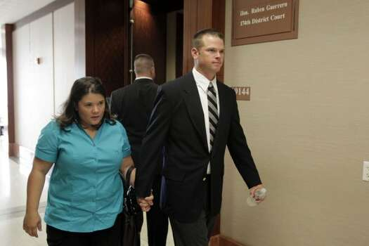 HPD officer Andrew Blomberg, right, walks out of the 174th District Court during a change of venue hearing at the Harris County Criminal Justice Center Monday, Aug. 22, 2011, in Houston. 