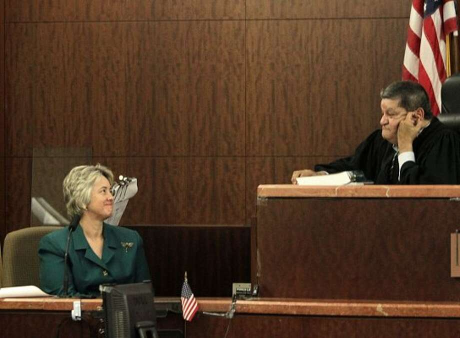 Mayor Annise Parker talks with judge Ruben Guerrero during a change in venue hearing where she said that she believes HPD officers, Andrew Blomberg, Phil Bryan, Raad Hasan and Drew Ryser videotaped beating a teenage burglary suspect will be able to get a fair trial in Houston as she testified in the 174th District Court at the Harris County Criminal Justice Center Monday, Aug. 22, 2011, in Houston. 
