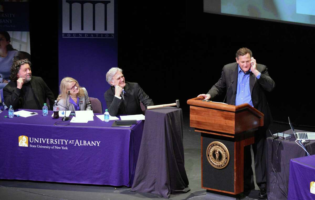 Co-founder of Tribeca Film Festival, Craig Hatkoff, at right, takes a cell phone call during a panel discussion on local film production at UAlbany Thursday May 3, 2012. From left are Philip Morris, CEO of Proctors, Patricia Swinney Kaufman, executive director of the New York State Governor's Office for Motion Picture and Television Development and Times Union editor Rex Smith. (John Carl D'Annibale / Times Union)
