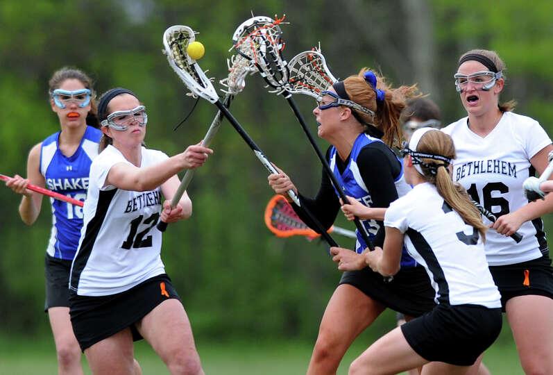 Bethlehem's Lauren DiFrancesco (12), left, battles Shaker's Lauren Smith (13), center, for the ball,