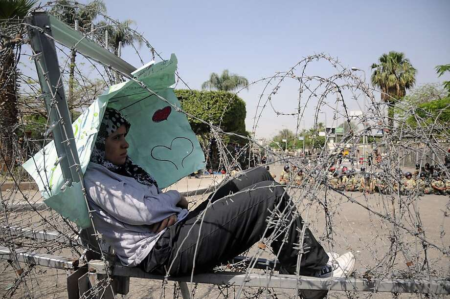 A protester rests on a barbed wire fence in Cairo, Egypt, Thursday, May 3, 2012. Nearly a dozen people were killed in clashes that broke out Wednesday when apparent supporters of the ruling military council attacked a mostly Islamist crowd staging a sit-in outside the Ministry of Defense in Cairo to call for an end to the generals' rule. (AP Photo/Mohammed Asad) Photo: Mohammed Asad, Associated Press