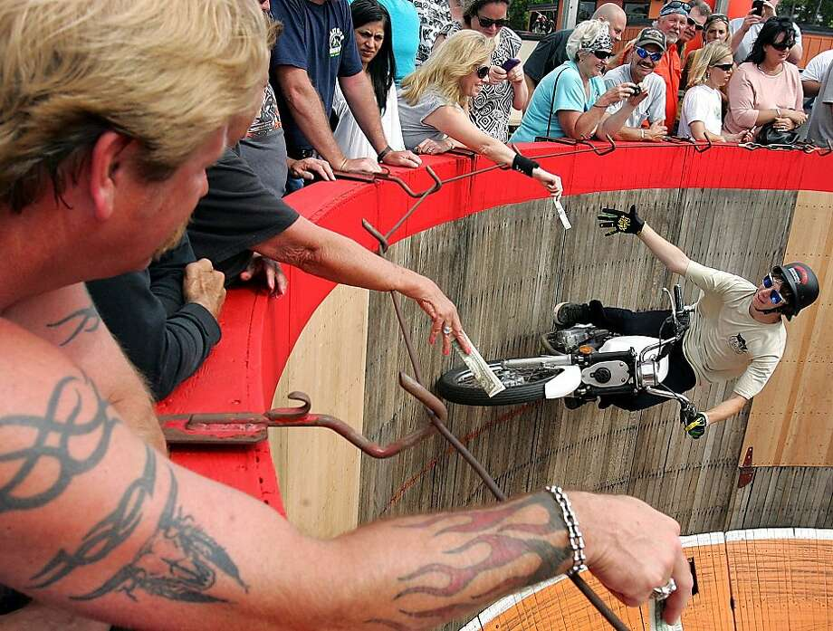 "Kyle Ives collects tips during the Ives Brothers ""Wall of Death"" motorcycle stunt show in Panama City Beach, Fla. on Thursday, May 3, 2012. (AP Photo/The News Herald/Panama City, Fla., Andrew Wardlow) MANDATORY CREDIT Photo: Andrew Wardlow, Associated Press"