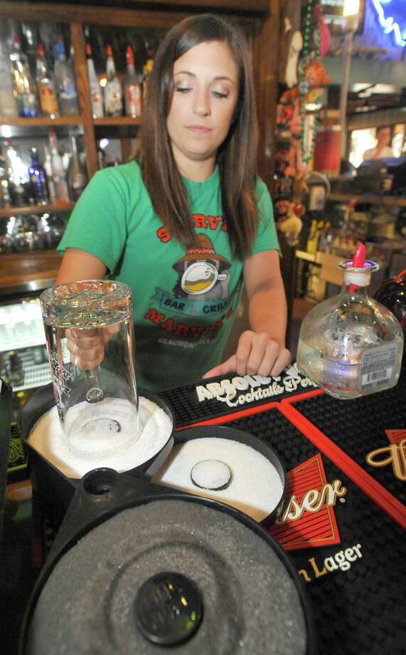 Bartender Jessica Graham at Starvin Marvin's on 11th Street makes  a Marvarita, which is a margarita made with St. Germain Liqueur and Patron Silver Tequila on April 24, 2012.  She starts by capping the glass with a layer of salt. Dave Ryan/The Enterprise Photo: Dave Ryan