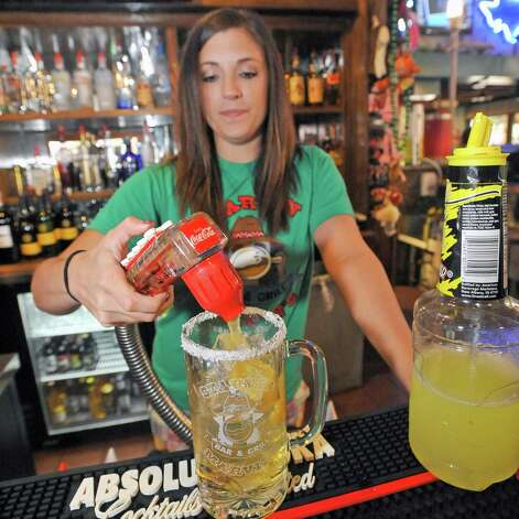 Bartender Jessica Graham at Starvin Marvin's on 11th Street makes  a Marvarita, which is a margarita made with one half oz. of St. Germain Liqueur, one half oz. of Grand Marnier Liqueur along with one and one half ounces of Patron Silver Tequila on April 24, 2012.   She then adds orange juice without the pulp to the mix. Dave Ryan/The Enterprise Photo: Dave Ryan