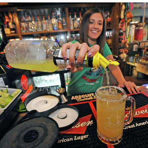 Bartender Jessica Graham at Starvin Marvin's on 11th Street makes  a Marvarita, which is a margarita made with one half oz. of St. Germain Liqueur, one half oz. of Grand Marnier Liqueur along with one and one half ounces of Patron Silver Tequila on April 24, 2012.   After adding the orange juice without the pulp to the mix, she then fills the glass with Sweet and Sour. Dave Ryan/The Enterprise Photo: Dave Ryan