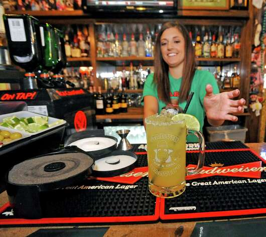 Bartender Jessica Graham at Starvin Marvin's on 11th Street makes  a Marvarita, which is a margarita made with one half oz. of St. Germain Liqueur, one half oz. of Grand Marnier Liqueur along with one and one half ounces of Patron Silver Tequila on April 24, 2012.   After adding the orange juice without the pulp to the mix, and the with Sweet and Sour, she then garnishes the glass with a lime and straw.  Dave Ryan/The Enterprise Photo: Dave Ryan