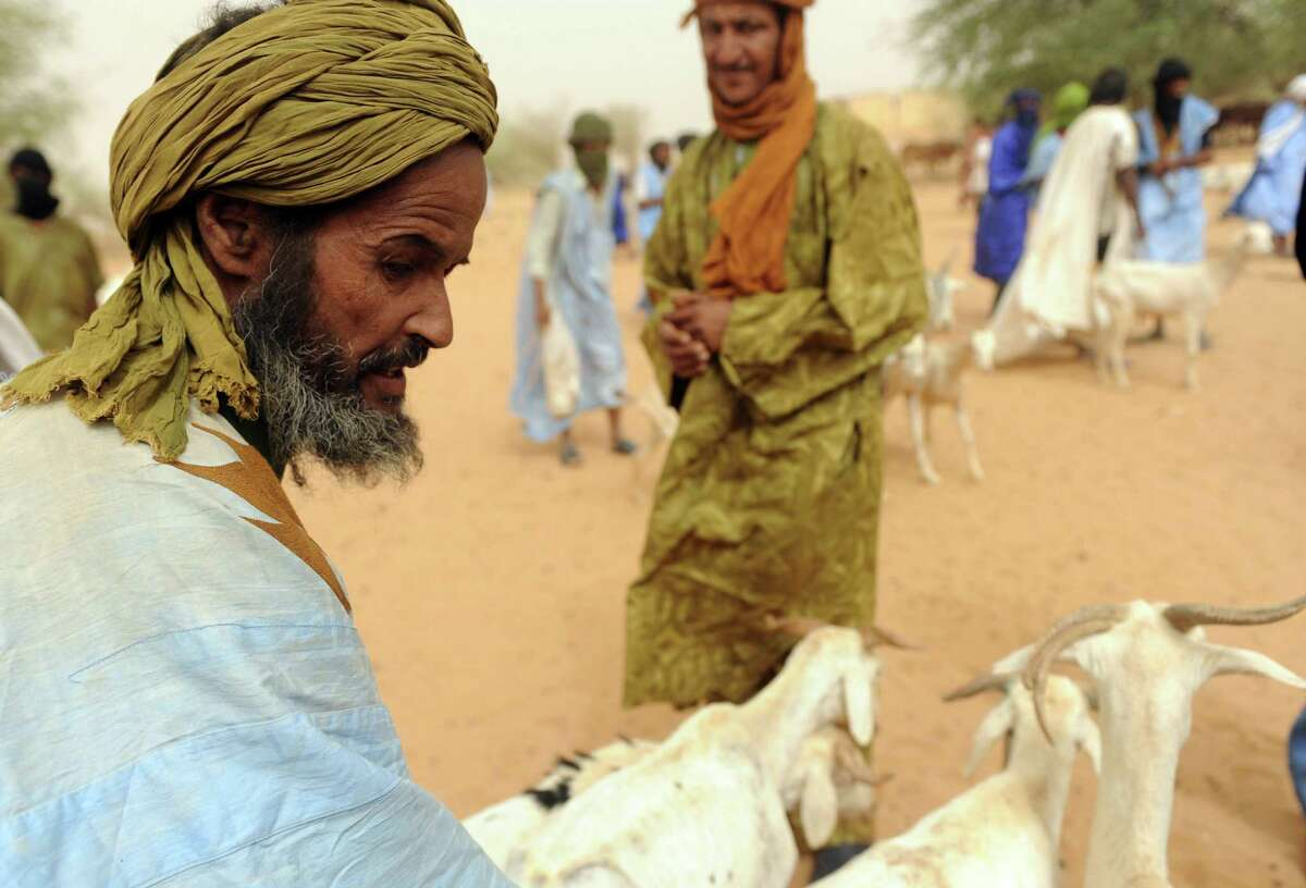 Malian shepherd Mahmoud Al Hassan, a refugee at Mbere refugee camp, near Bassiknou, southern Mauritania, sells goats at the Jmaa market. (ABDELHAK SENNA/AFP/GettyImages)