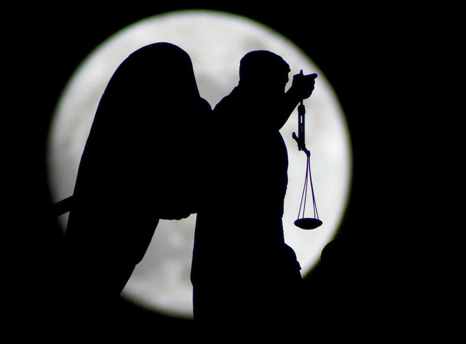 A statue of an angel fixed at the St. Isaak's Cathedral is silhouetted by the rising moon in St.Petersburg, Russia, Friday, March 18, 2011. The world will see a supermoon on March 19, and the full moon will make the sight even more interesting. The moon will pass the Earth at the distance of 365,600 kilometers, the closest in the past 19 years. (AP Photo/Dmitry Lovetsky) Photo: Dmitry Lovetsky, STF / AP2011
