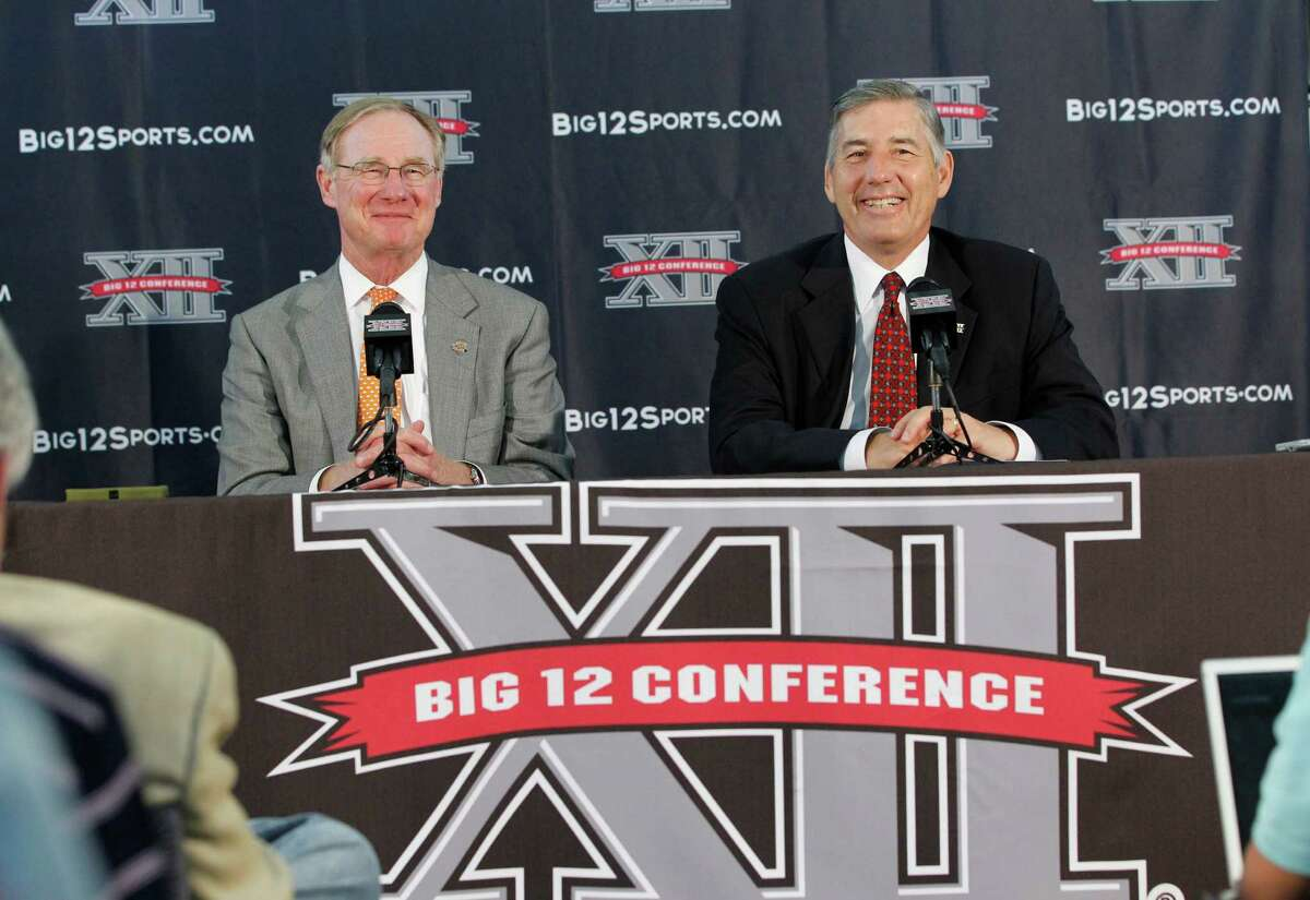 New Big 12 Conference Commissioner Bob Bowlsby, right, smiles at a news conference where he was introduced to the media at Big 12 headquarters Friday, May 4, 2012, in Irving, Texas. At left is Oklahoma State University President Burns Hargis