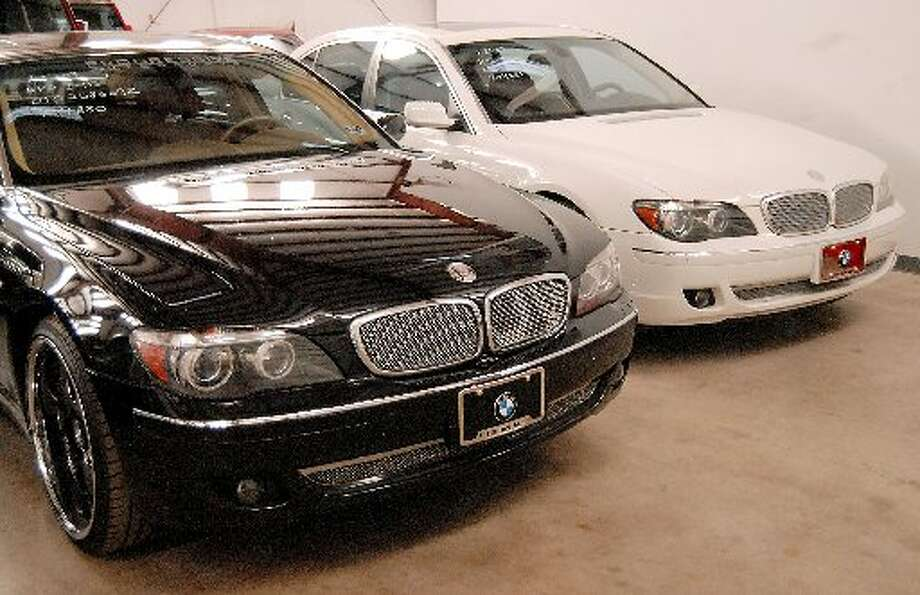 A black and white pair of 2006 BMW 760Li's belonging to reputed drug boss Raul Madrigal sit at a storage facility (Houston Chronicle)