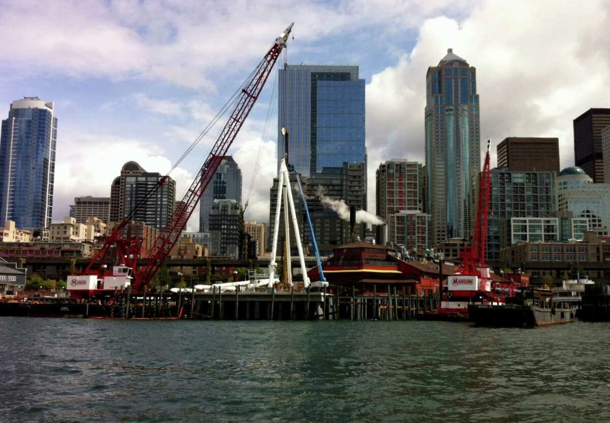 Supporting legs of the Seattle Great Wheel, a 175-foot tall Ferris wheel, are hoisted with a crane as seen from an Argosy Cruise on Friday. The structure will dramatically change the Seattle skyline.