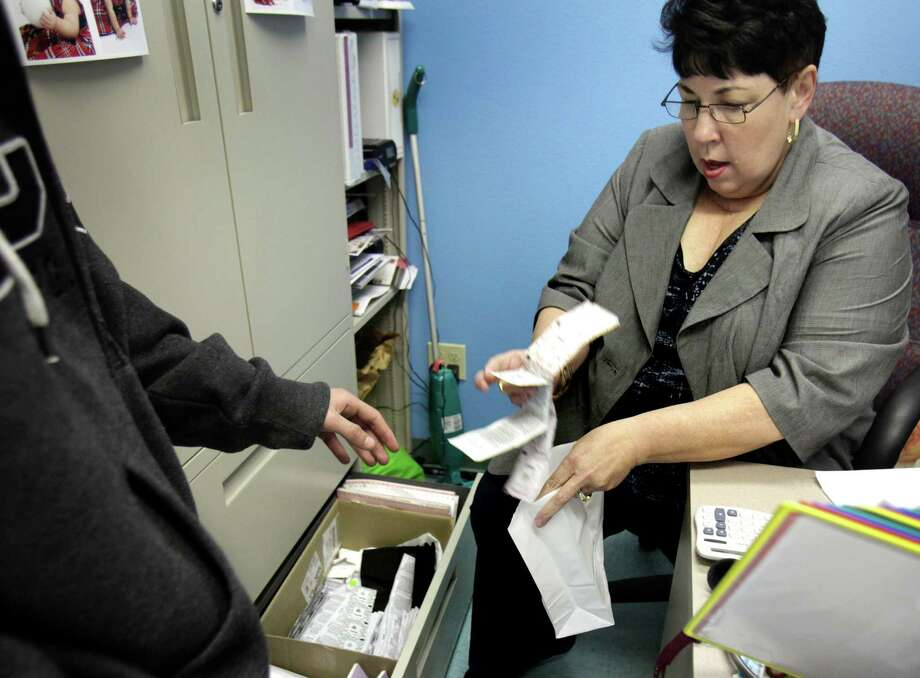 Sherry Hefner-Medrano, Nurse at the Health Clinic at Roosevelt High School in Los Angeles, hands out condoms to a male student in her office. Photo: Bob Owen, San Antonio Express-News / © 2012 San Antonio Express-News