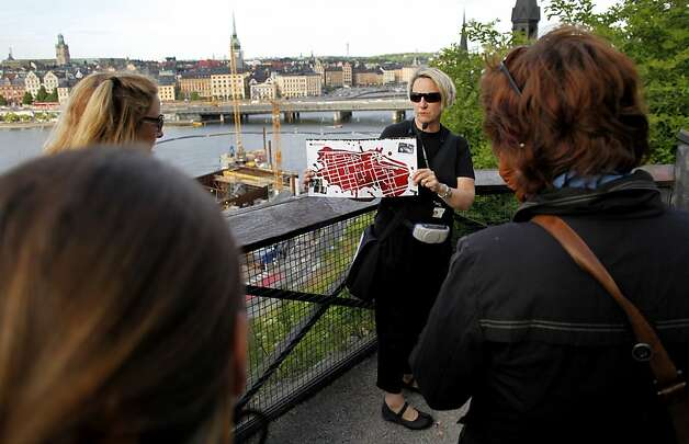 "Tour guide Eva Palmqvist, center, shows a map of the island of Sodermalm during a Stieg Larsson tour on Wednesday, June 16, 2010, in Stockholm, Sweden. Fans of the late crime novelist Stieg Larsson are getting lost in the Swedish countryside, searching for the quaint town of Hedestad featured in ""The Girl with the Dragon Tattoo."" Photo: Niklas Larsson, AP"